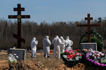 Grave diggers gather after burying a coronavirus disease victim at a graveyard in Saint Petersburg