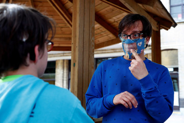 Educator Nicolas, wearing a partially transparent mask, uses sign language to communicate with a student at the Royal Institute for the Deaf Mute, amid the coronavirus disease (COVID-19) outbreak, in Brussels