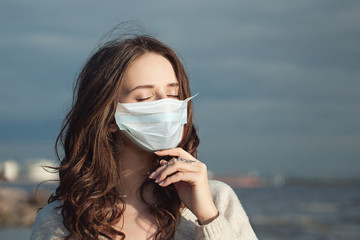 Beautiful woman in protective mask enjoying summer sun outdoors Wall mural