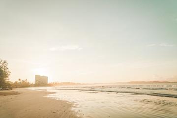 Świetlisty zachód słońca na tropikalnej plaży.
