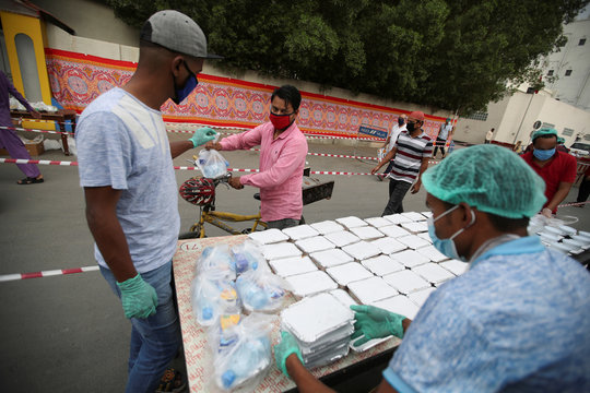 Volunteers wearing protective face masks and gloves, hand out Iftar meals provided by the authorities, following the outbreak of the coronavirus disease (COVID-19), during the holy month of Ramadan, in Manama