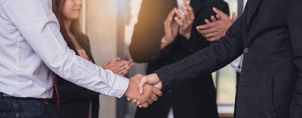 Businessperson handshaking together and colleagues applaud congratulating coworker with promotion...