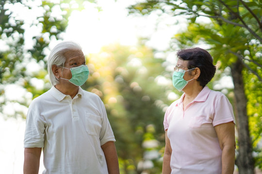 Asian elderly couple wearing surgical mask while walking in the park and keep social distancing during  covid-19 outbreak