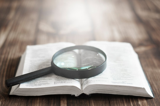 Open bible on a wooden table. Magnifier