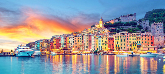 Poster de jardin Europe Méditérranéenne Mystic landscape of the harbor with colorful houses and the boats in Porto Venero, Italy, Liguria in the evening in the light of lanterns at sunset