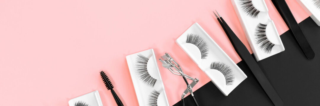 Various tools for eye lash extensions on a trendy pastel pink and black background. Banner. Concept. Eyelash curler, tweezers. Makeup accessories. Cosmetics. Fake eyelashes. Place for text. Top view.