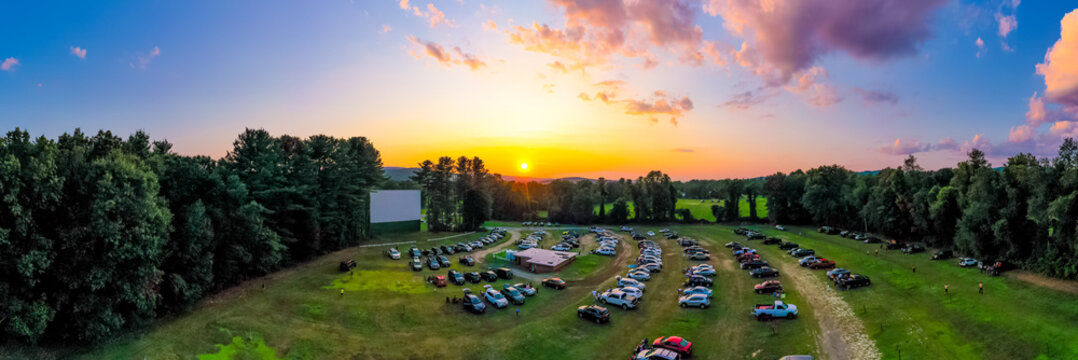 Panorama of outdoor drive-in movie theater at sunset with cars parked in field. Aerial photo taken at Northfield Drive-In.