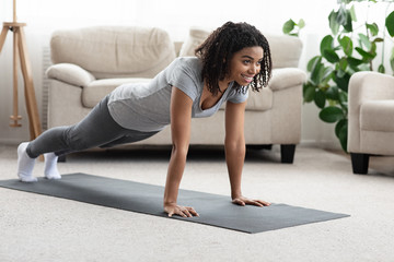 Domestic Workout. Young Sporty Black Woman Doing Plank Exercise At Home