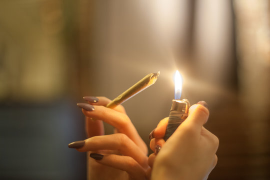 Young woman with pretty manicured nails is holding a lighter and about to spark and light a legal pre rolled marijuana bud joint in organic hemp rolling papers for THC smoking