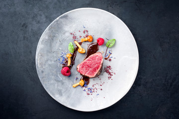Barbecue dry aged wagyu beef fillet head medallion steak natural with forest fruits, mushrooms and hot chili sauce as top view on a modern design plate with copy space