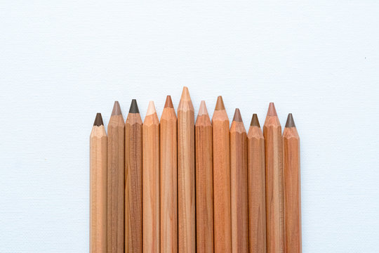 Diferents neutral color skin pencils aligned on a white canvas