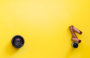Flat lay view of retro camera lens and film strip over pastel coloured yellow background with copy...