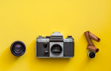 Flat lay view of retro camera, lens and film strip over pastel coloured yellow background with copy...