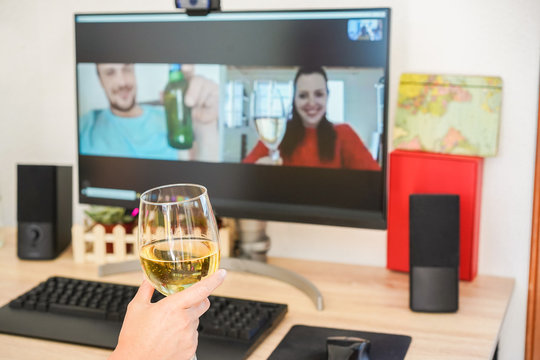Young woman chatting and drinking wine on video call meeting room with friends - Alternative party during stay safe at home and isolation quarantine - Focus on glass