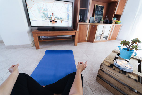 Young woman doing yoga at home while watching video tutorial on web app - Girl meditate and relax during isolation quarantine - Healthy lifestyle and fitness concept - Focus on right hand