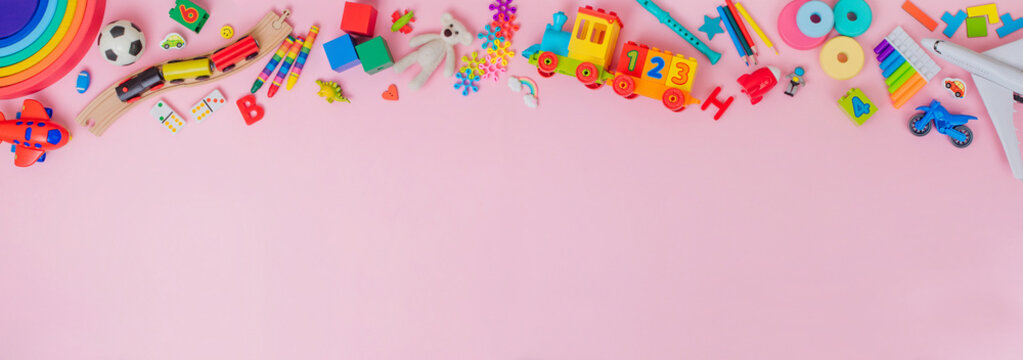 Frame of plastic and wooden kids toys on pink background