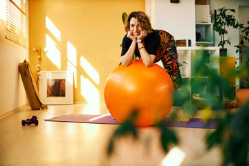 Cute smiling pregnant woman in forties leaning on pilates ball and looking at camera while standing at home in the morning.