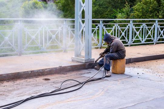 Worker with protective mask sandblasting of metal bridge