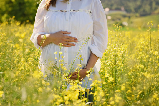 young pregnant woman in a field of oilseed