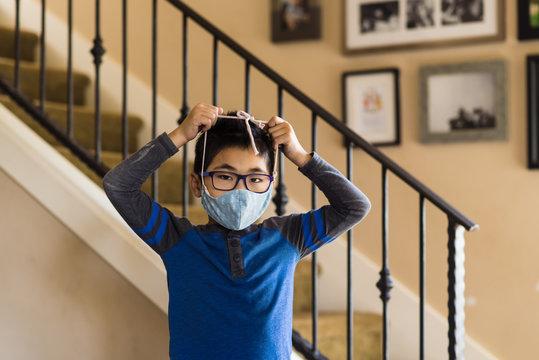 Asian boy pulls cloth mask over head