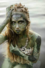 Fotobehang Schilderkunstige Inspiratie girl mermaid amphibian with green skin with body art with a necklace and a seashell swimsuit around her neck holding her hand to her serious face in the river summer in the water in the lake