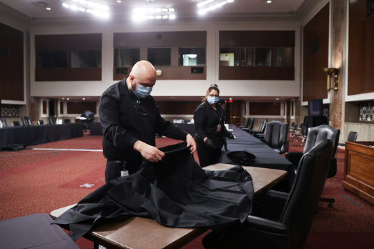 Workers clean between Senate committee hearings on Capitol Hill during the coronavirus outbreak in Washington