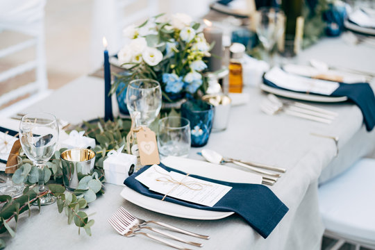 Wedding dinner table reception. A square plate with a blue cloth towel, knives and forks next to the plate. Flower composition with eucalyptus leaves in the center of the table and burning candles.