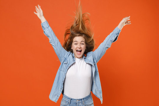Cheerful young woman girl in casual denim clothes posing isolated on orange wall background studio portrait. People lifestyle concept. Mock up copy space. Having fun, jumping with fluttering hair.
