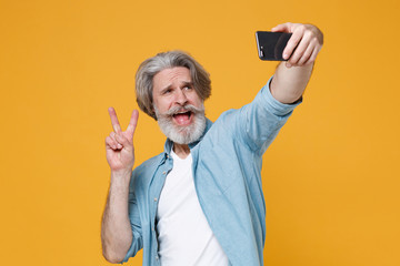 Funny elderly gray-haired mustache bearded man in casual blue shirt isolated on yellow background. People lifestyle concept. Mock up copy space. Doing selfie shot on mobile phone showing victory sign.