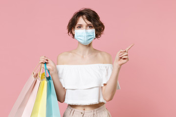 Young woman girl in summer clothes sterile face mask hold package bag with purchases isolated on pink background. Shopping discount sale concept. Mock up copy space. Pointing index finger aside up.