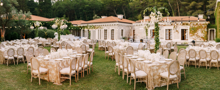 Wedding dinner table reception. Elegant tables for guests with cream tablecloths with patterns, on green lawn, with garlands and chandeliers hanging over them. Chairs with round back