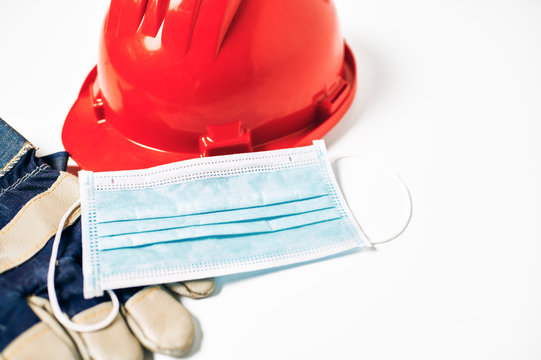 Worker's helmet and gloves next to antiviral mask on white background