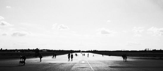 Fotomurales - People At Airport Runway Against Sky