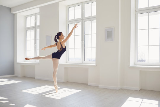 Ballerina. Young graceful ballet dancer is rehearsing a performance in a white studio with windows.