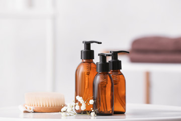Different shower gels, brush and flowers on table in bathroom