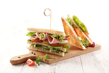 club sandwich with ham, tomato, lettuce and cucumber on wooden board