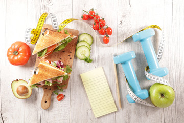 Fototapete - club sandwich, dumbbell and meter tape- diet plan concept
