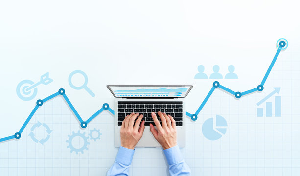 Web analytics and digital marketing. Top view of business man using laptop. Blue graphs and icons.