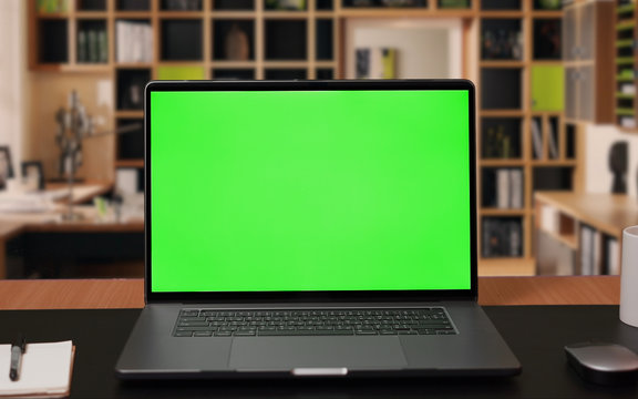 Laptop computer with Green screen Mock-up on working desk in office with no people
