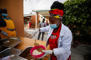 Volunteers and teachers serve food at a school feeding scheme in Gugulethu township during a nationwide lockdown aimed at limiting the spread of coronavirus disease (COVID-19) in Cape Town