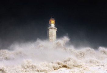 lighthouse at night with storm and waves splashing