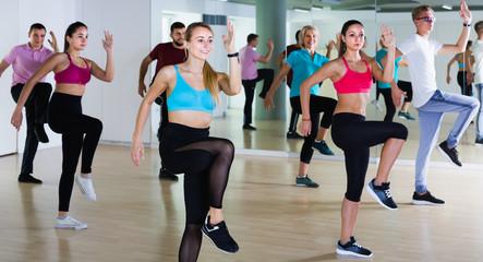 joyous men and ladies dancing aerobics at lesson