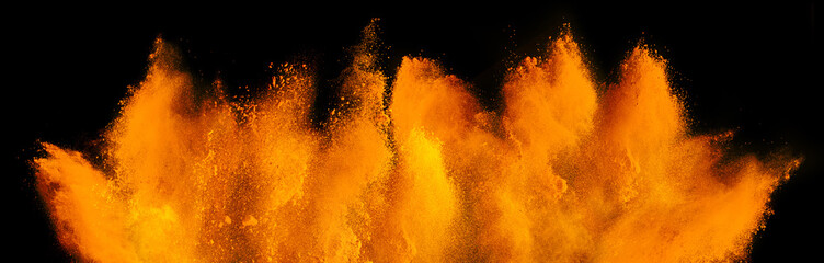 orange red holi paint color powder explosion isolated dark black background. industry beautiful...