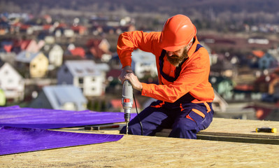 Materials requirements. Install partially overlapping layers of material over roof insulation surfaces. Master repair roof. Flat roof installation. Roofer constructing roof. Man roofing surface