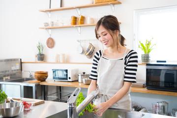Fototapeta キッチンで料理を作る若い女性 obraz