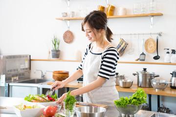 キッチンで料理を作る若い女性