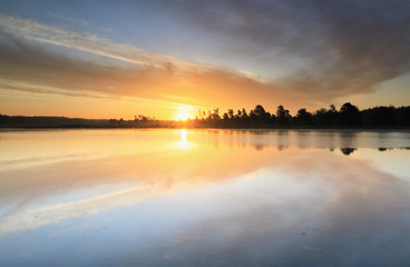 Wall Mural - beautiful sunrise reflected in big forest lake