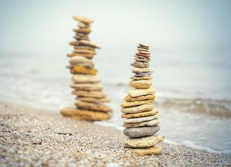 Photo sur Plexiglas Zen pierres a sable Stones pyramid on sand symbolizing zen, harmony, balance. Ocean in the background. Soft focus.