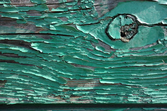 türkisfarbener Lack blättert von einem Holzbrett ab