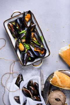 Mussels or clams, shellfish in a bowl on light background, text space. Overhead view.